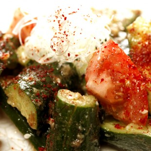 Some pieace of cucumbers and tomatos on the dish with sesame oil