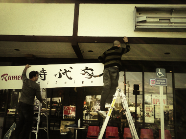 Workers trying to put the JIDAIYA's front sign board on the frame.